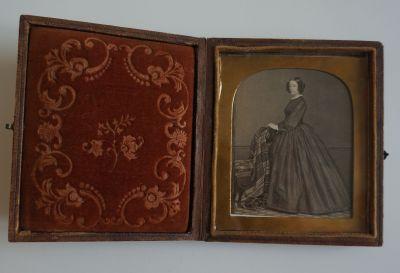 Sophie de Ségur debout de trois-quarts, mains posées sur le dossier d'une chaise recouvert d'un plaid